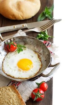 Ovo frito com tomate, pão caseiro e ervas em uma velha frigideira na madeira close-up