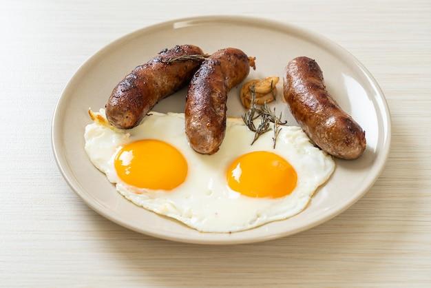 Ovo frito duplo caseiro com linguiça de porco frita - no café da manhã