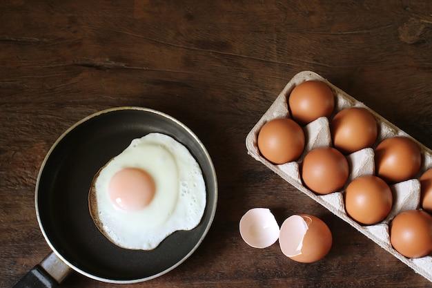 Ovo frito e ovos na tabela de madeira.