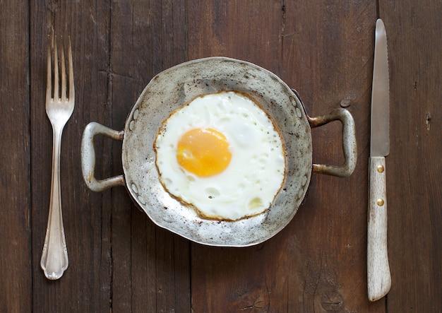Ovo frito em uma frigideira velha com garfo e faca na vista superior da madeira