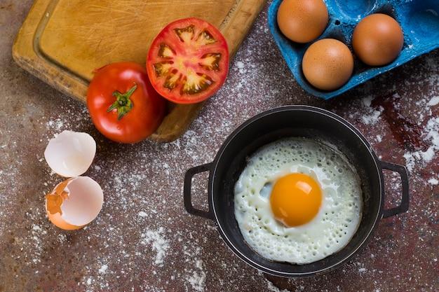 Ovo frito em uma panela ou panela acompanhado de tomate e ovos frescos em uma tábua e farinha