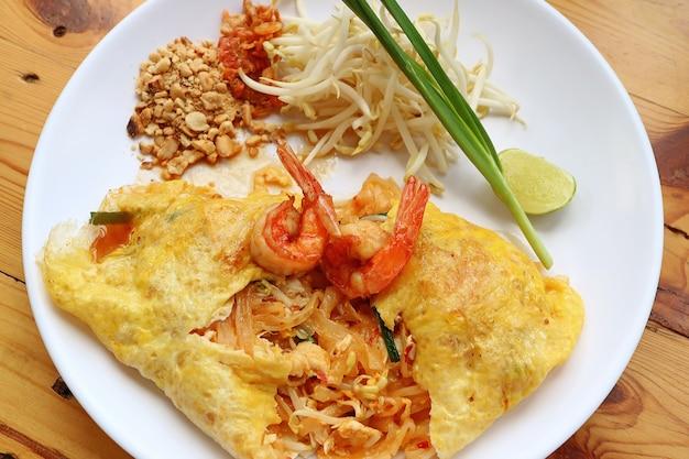 Ovo frito estilo tailandês envolto stir fried noodle ou pad thai coberto com camarões servido
