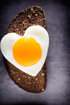 Ovo frito na fatia de pão em forma de coração.