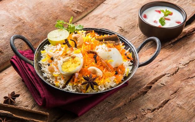 Ovo indiano biryani ou arroz anda servido em kadhai ou kadai com molho de iogurte, foco seletivo
