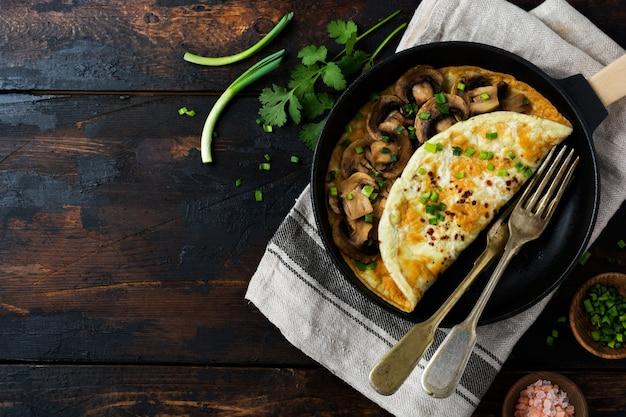 Ovo mexido fresco, omelete ou fritada com cogumelos, cebola e ervas frescas em frigideira de ferro fundido. vista superior com espaço de cópia.