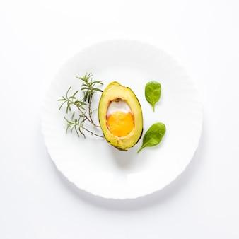 Ovo orgânico caseiro cozido em abacate com folhas no fundo branco