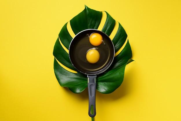 Ovo orgânico na panela sobre folha de monstera em fundo amarelo