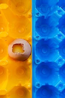 Ovo quebrado em um recipiente amarelo brilhante. fundo abstrato branco. casca de ovo e yelk yelow