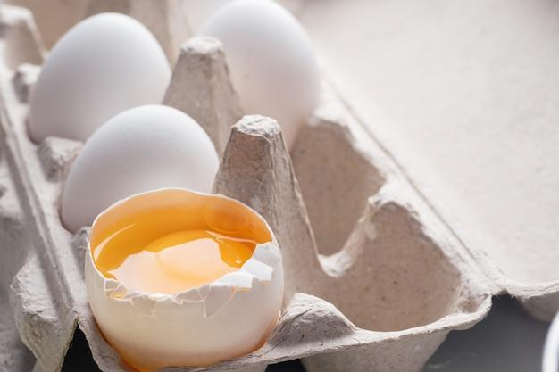 Ovo quebrado, gema, close-up. ovos em caixa de papelão, embalagem ecológica. cozinhar na cozinha, em casa. fundo.
