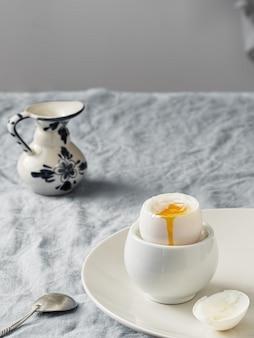 Ovo quente, café da manhã leve. prato de cerâmico branco com ovo quente, em um prato de cerâmico branco, numa toalha de mesa azul.