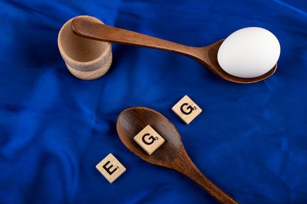 Ovo único cru com colheres de madeira e letras de madeira em tecido de cetim azul.