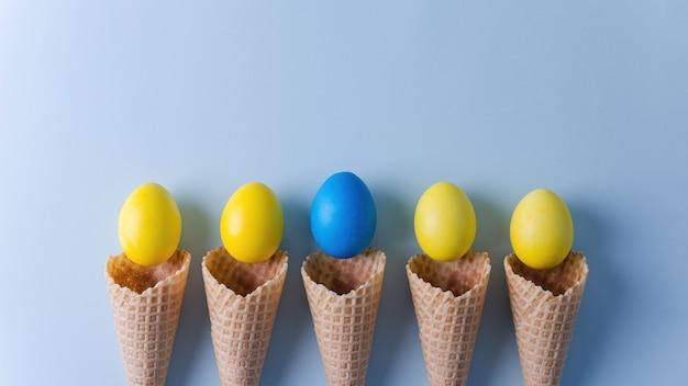 Ovos amarelos e um azul em cones de waffle encontram-se em um fundo horizontal azul.