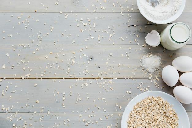Ovos; aveia; leite; farinha; e açúcar no fundo de madeira