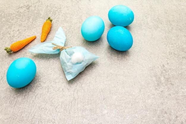 Ovos azuis para a páscoa com coelho de papel e cenoura de malha