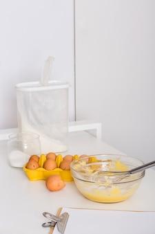 Ovos batidos; caixa de ovos; farinha; sal e papel na área de transferência na mesa