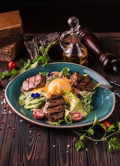 Ovos benedict com carne bovina em um grande prato branco