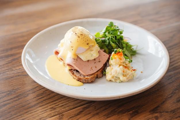 Ovos benedict com presunto, torradas e purê de batata. servido com salada em um prato branco na mesa de madeira.
