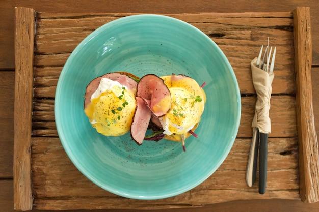 Ovos benedict no fundo da placa de madeira