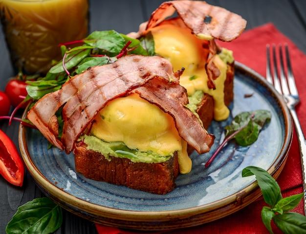 Ovos benedict - torrados, bacon, ovos pochê e um delicioso molho holandês amanteigado. um restaurante