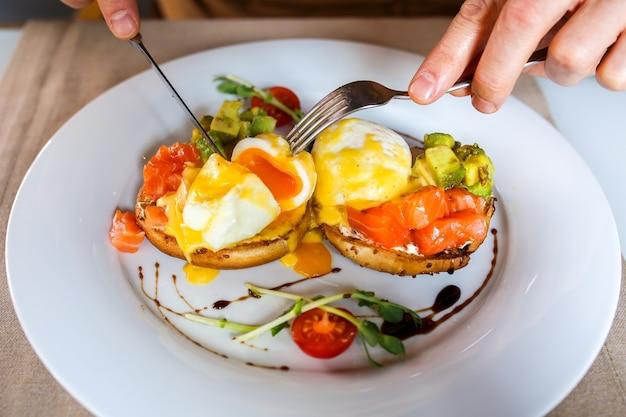 Ovos benedicto ovo escalfado é cortado com uma faca prato de café da manhã ovos benedict em torradas closeupcafé da manhã delicioso com ovo benedicto ovo está se espalhando homem tomando café da manhã com garfo e faca