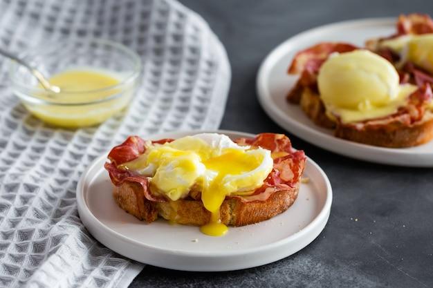 Ovos bento - pão inglês torrado, presunto parm, ovos escalfados com molho holandês e limão na cinza