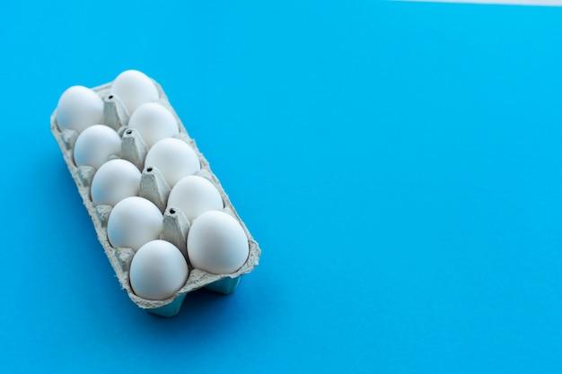 Ovos brancos da galinha em uma caixa de cartão aberta. uma dúzia de ovos em embalagens ecológicas