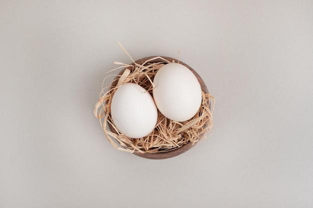 Ovos brancos de frango fresco com feno em uma tigela de madeira.