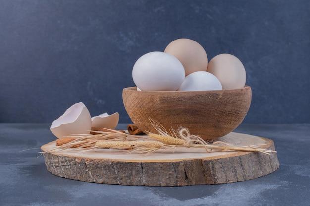 Ovos brancos e cascas de ovo em uma bandeja de madeira.