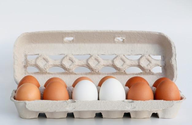Ovos brancos e marrons em caixa de papelão