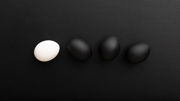 Ovos brancos e pretos em uma mesa escura