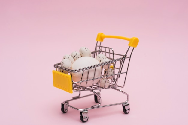 Ovos brancos em carrinho de supermercado na mesa