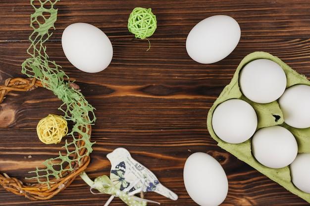 Ovos brancos em rack com pequenas bolas na mesa