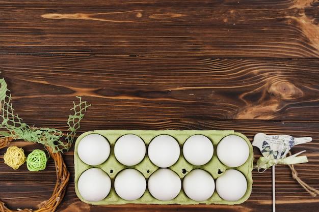 Ovos brancos em rack na mesa de madeira