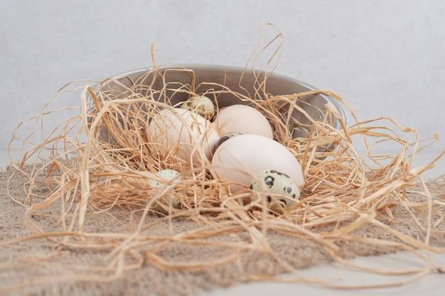 Ovos brancos frescos de frango com ovos de codorna e feno na placa cinza.