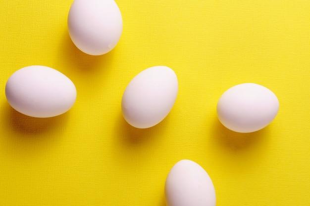 Ovos brancos orgânicos em um cru no backgound amarelo.