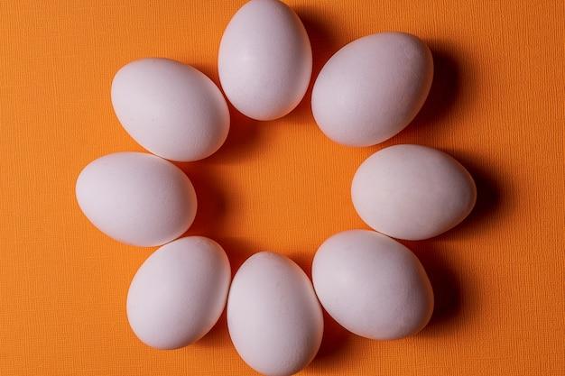Ovos brancos orgânicos em um cru no backgound pastel alaranjado.