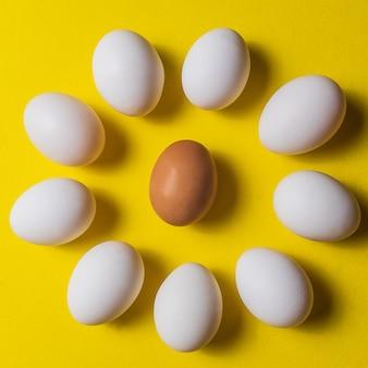 Ovos brancos orgânicos em um cru no backgound pastel amarelo.