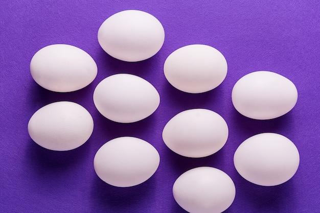 Ovos brancos orgânicos em um cru no backgound pastel.