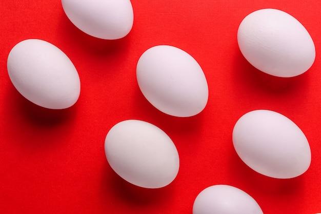 Ovos brancos orgânicos em um cru no backgound vermelho.