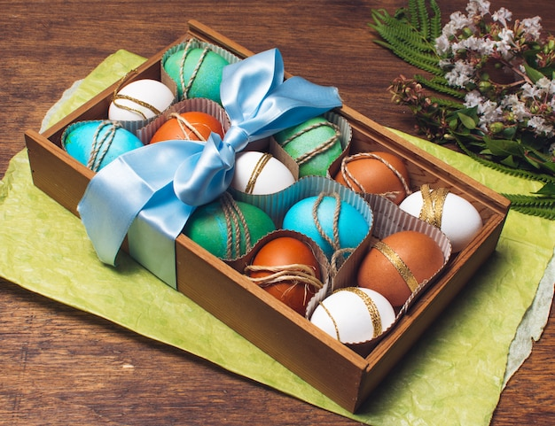 Ovos brilhantes em caixa em papel ofício perto de monte de plantas