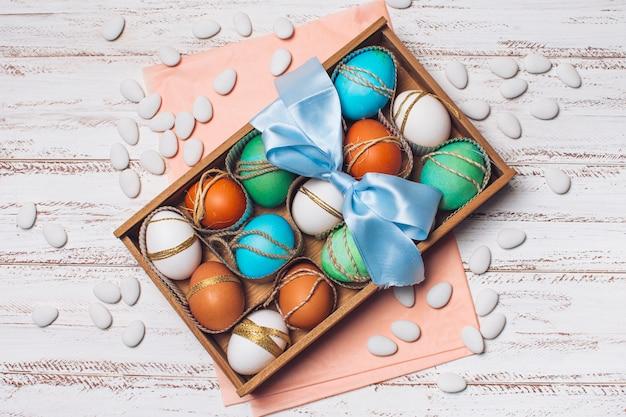 Ovos brilhantes em caixa em papel ofício rosa perto de pequenas pedras