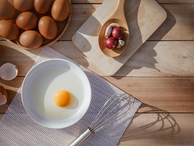 Ovos caem em bandejas de madeira e quebram ovos.