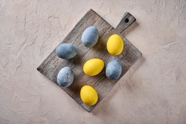 Ovos caseiros de páscoa coloridos de mármore amarelo e cinza na placa de corte envelhecida de madeira cópia espaço