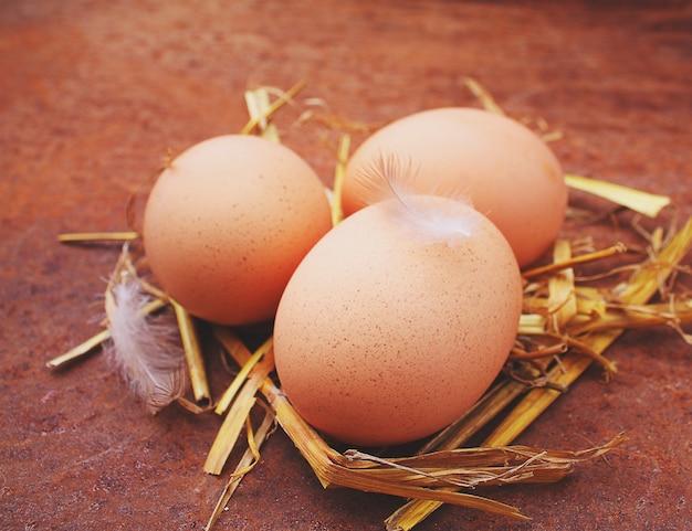 Ovos caseiros em uma palha em um fundo velho.