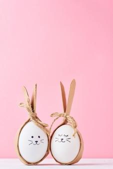Ovos caseiros engraçados com caras em um fundo rosa. conceito de páscoa