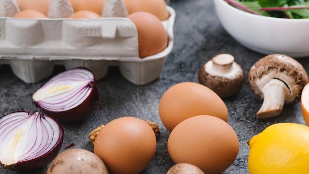 Ovos; cebola cortada ao meio; cogumelo; limão e ovos na bancada da cozinha cinza