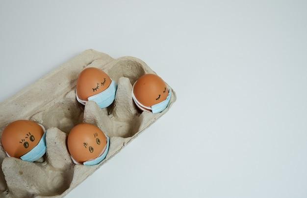 Ovos colocados no conceito de quarentena de máscara facial durante a páscoa ovos de páscoa em uma máscara médica