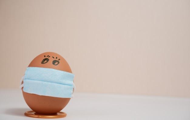Ovos colocam máscara facial - conceito de quarentena durante a páscoa. ovos de páscoa em uma máscara médica. conceito de auto-isolamento.