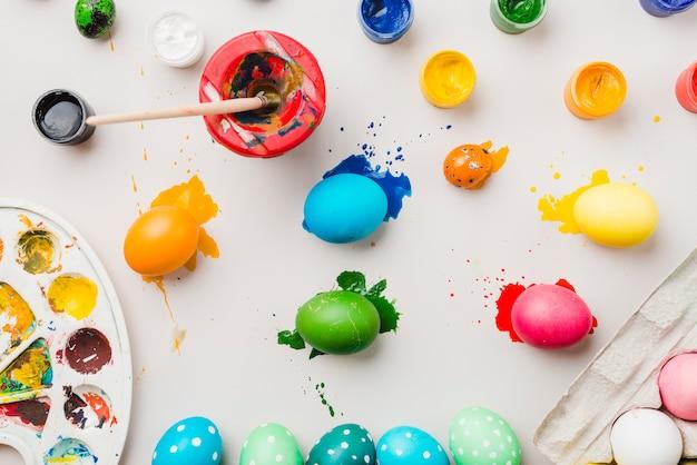 Ovos coloridos brilhantes perto de recipiente, pincel em lata, cores de água e paleta