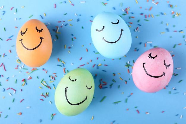 Ovos coloridos com sorrisos pintados cartão de feliz páscoa.